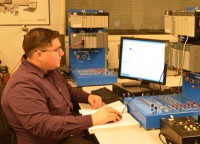 Robert Ruiz operates the 5150 Robo CIM in his lab class for industrial technology. The equipment is held in the computer integrated manufacturing lab.