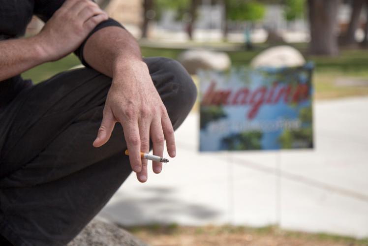 A+student+smokes+while+posing+near+%E2%80%9CBCTobaccoFree%E2%80%9D+ad.%0A