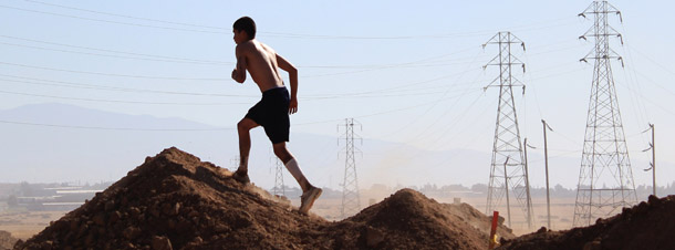 A participant runs up a pile of dirt at the annual Volkslauf Mud Run