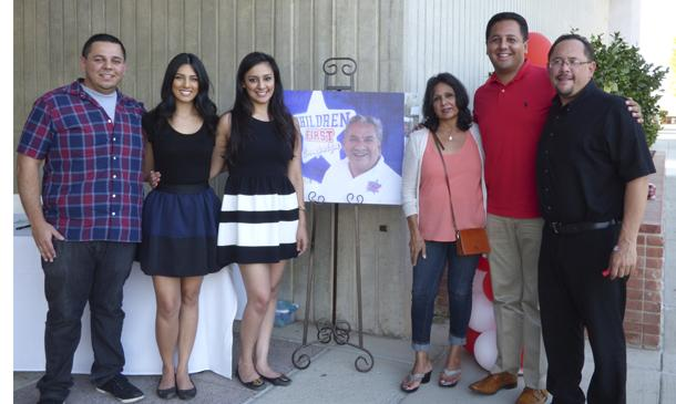 Widow+Rachel+Gonzales+poses+with+her+children+around+a+photo+of+Manuel+Gonzales+Jr.+at+the+scholarship+fundraiser+event.+Manuel+passed+away+earlier+this+year+and+was+a+counselor+at+Bakersfield+College+for+37+years.