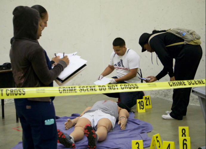 From left to right: Emm West, Naomi Valladares, Richard Tovar and Elexus Thurman examine the mock murder scene on March 23.