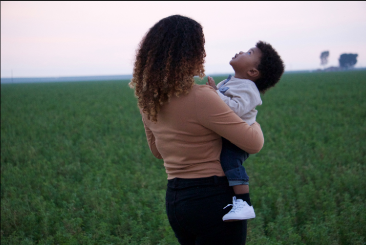 Joseline+Pinto+stands+in+a+field+while+holding+her+child+as+he+gazes+up.