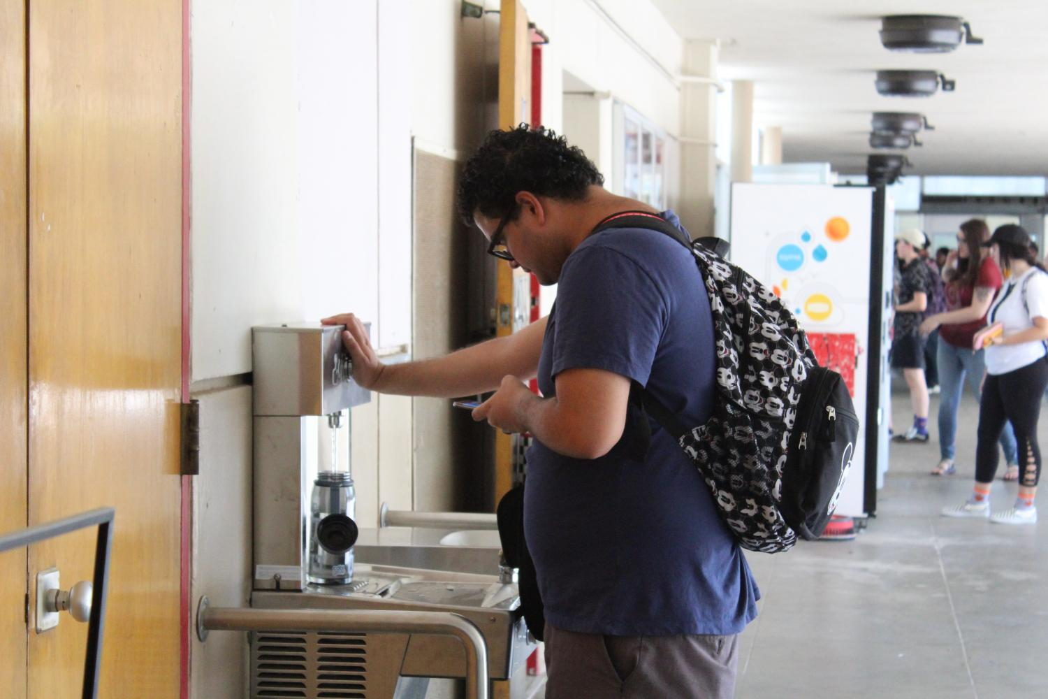 A student is shown standing while filling up his water bottle with the new fountain.
