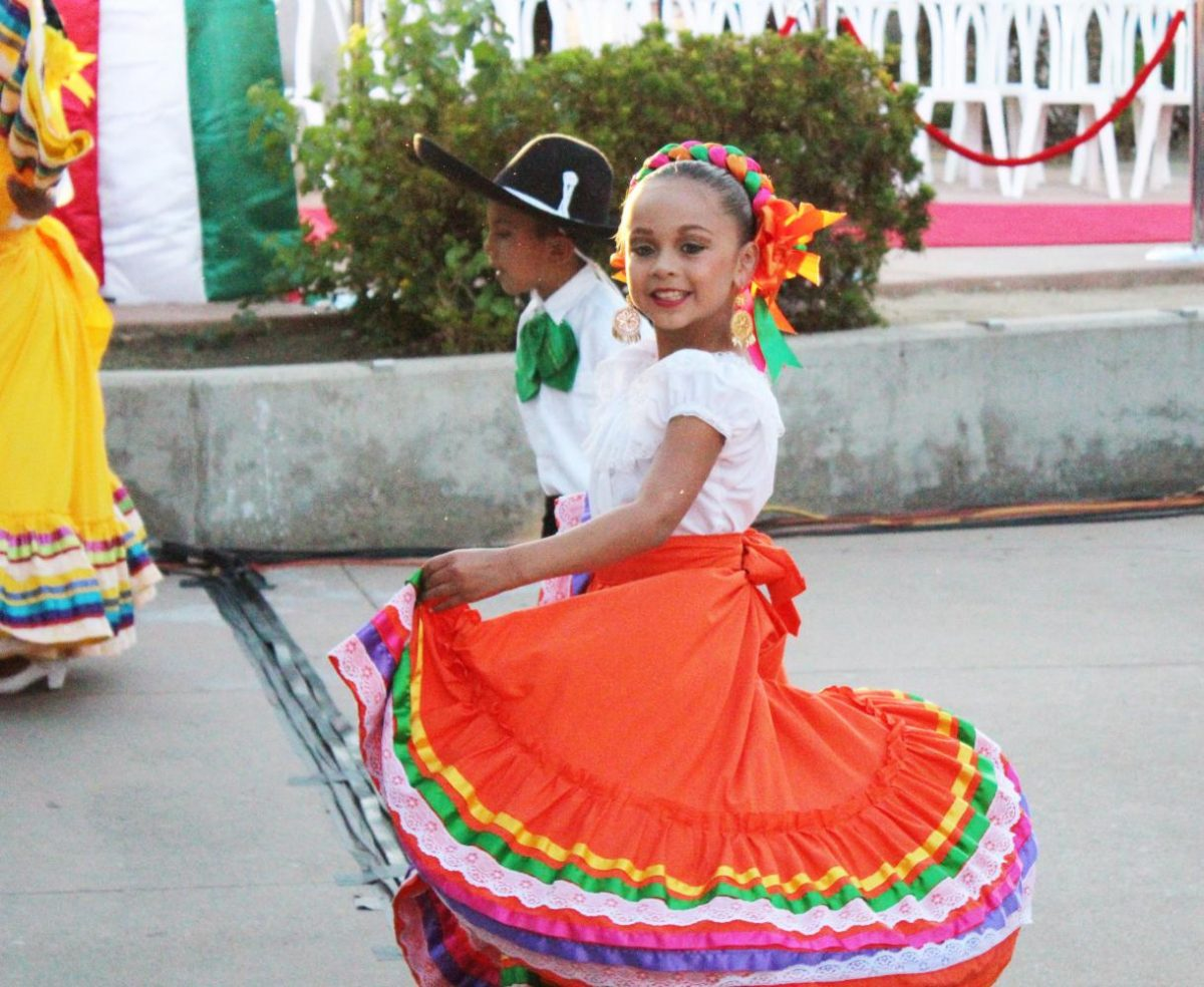 A+little+girl+smiles+as+she+twirls+her+skirt+during+a+traditional+Mexican+dance+routine.%0A