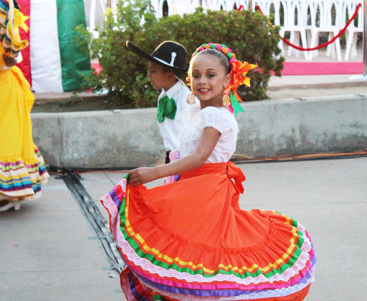 A little girl smiles as she twirls her skirt during a traditional Mexican dance routine.