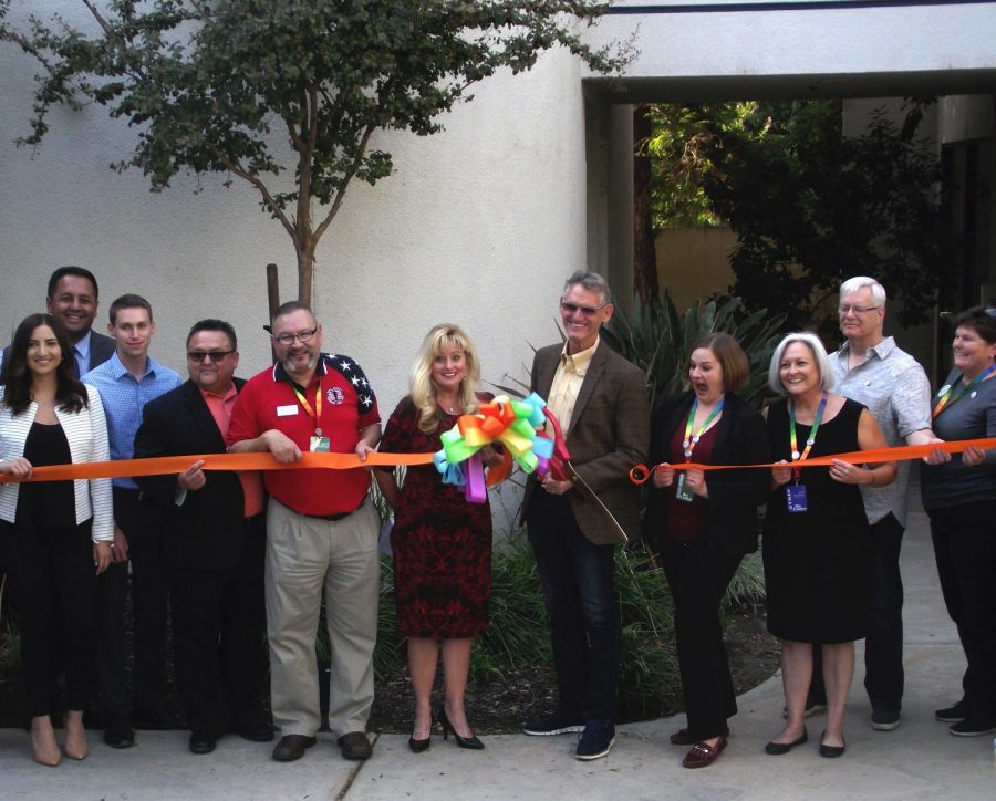 Guests pose and smile as Vice Mayor and Ward 4 councilman Bob Smith cuts the ribbon for the opening of the newAnnex of the Gay and Lesbian Center in Bakersfield.
