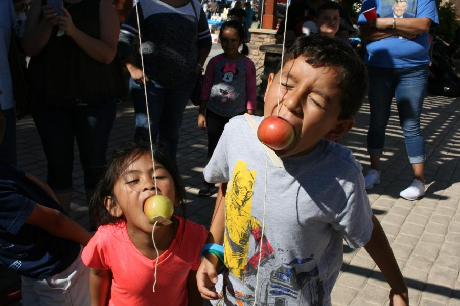 Two children compete in the apple bobbing contest.