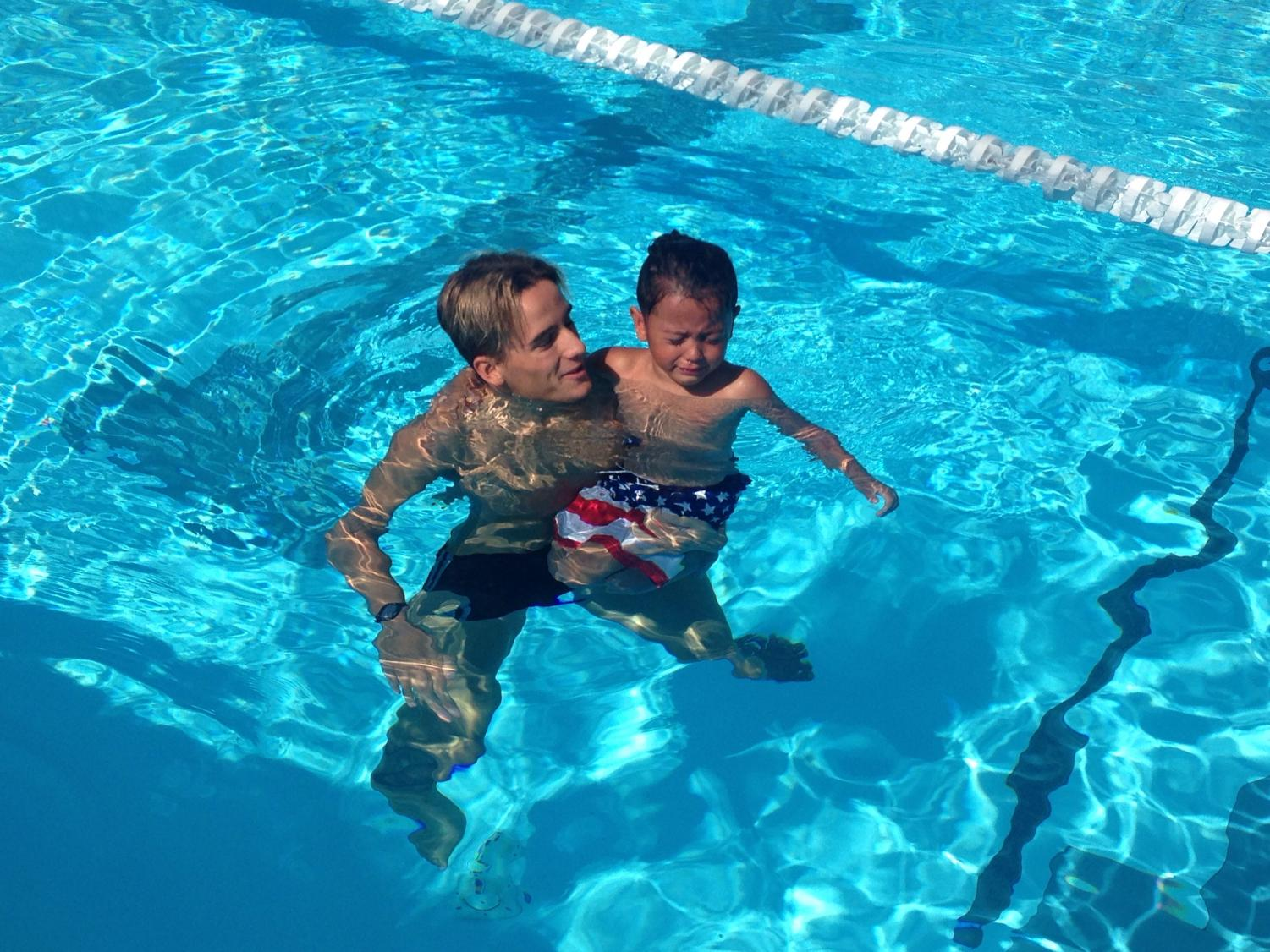 Tanner Lopes, a member of the Bakersfield College swim team teaches Braylen Davis how to be comfortable in the water.