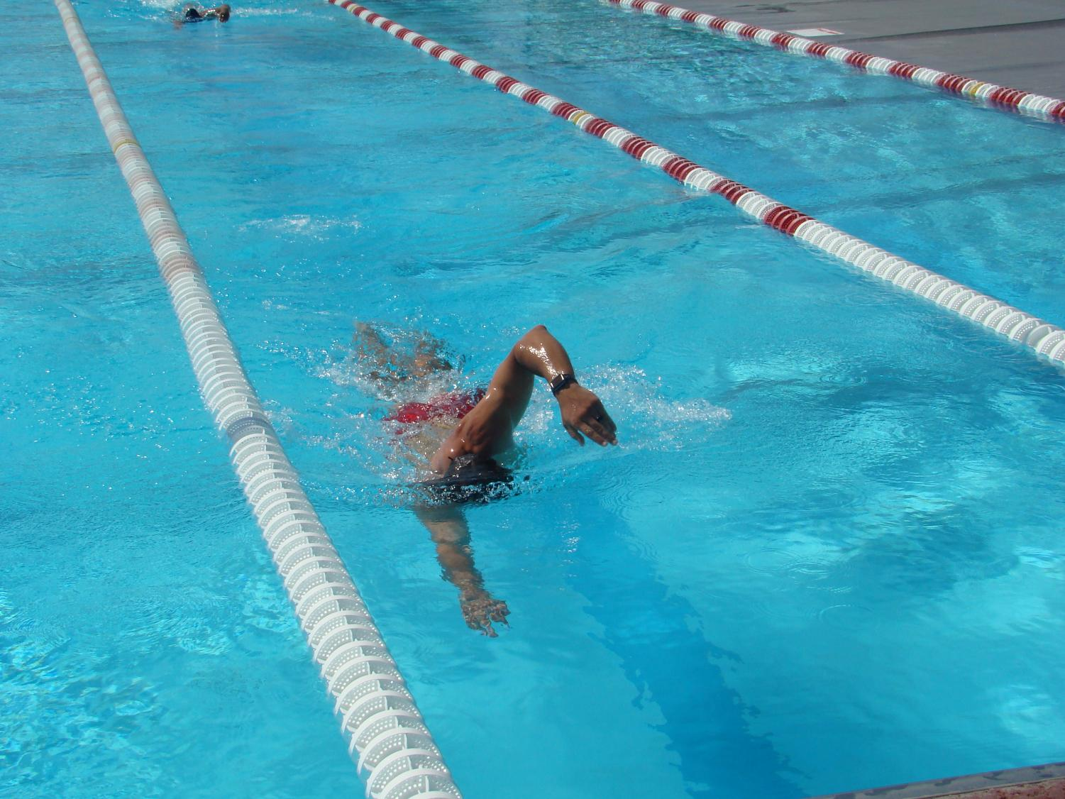 Mark Moon, the head coach of the men's and women's Bakersfield College swim teams, shows off his technique during the swimming relay.