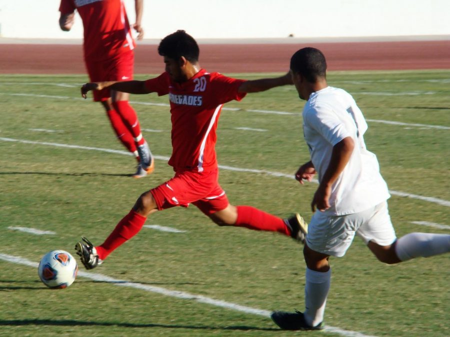 BC Midfielder Carlos Melendez kicks the ball while LA Mission's player tries to take it from him.