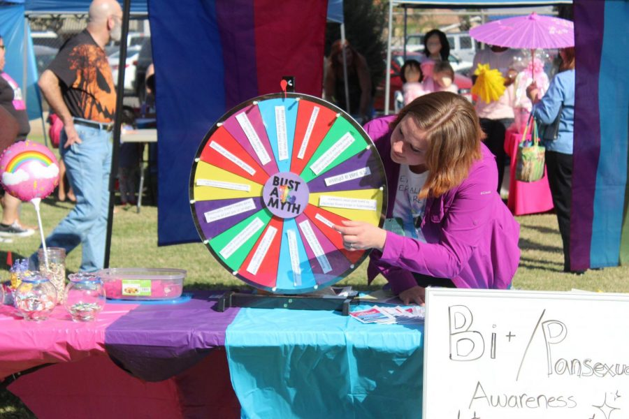 Emily Fisher makes sure that her stand is in order for her Bi and Pansexual awareness stand.