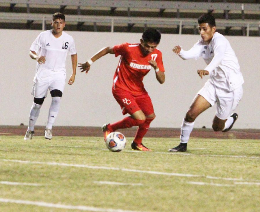 Jose Daniel Guerrero fights to keep the ball in his play from two Citrus College players.