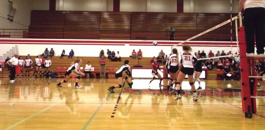 A BC player leans down to bump the volleyball as her teammates look on.