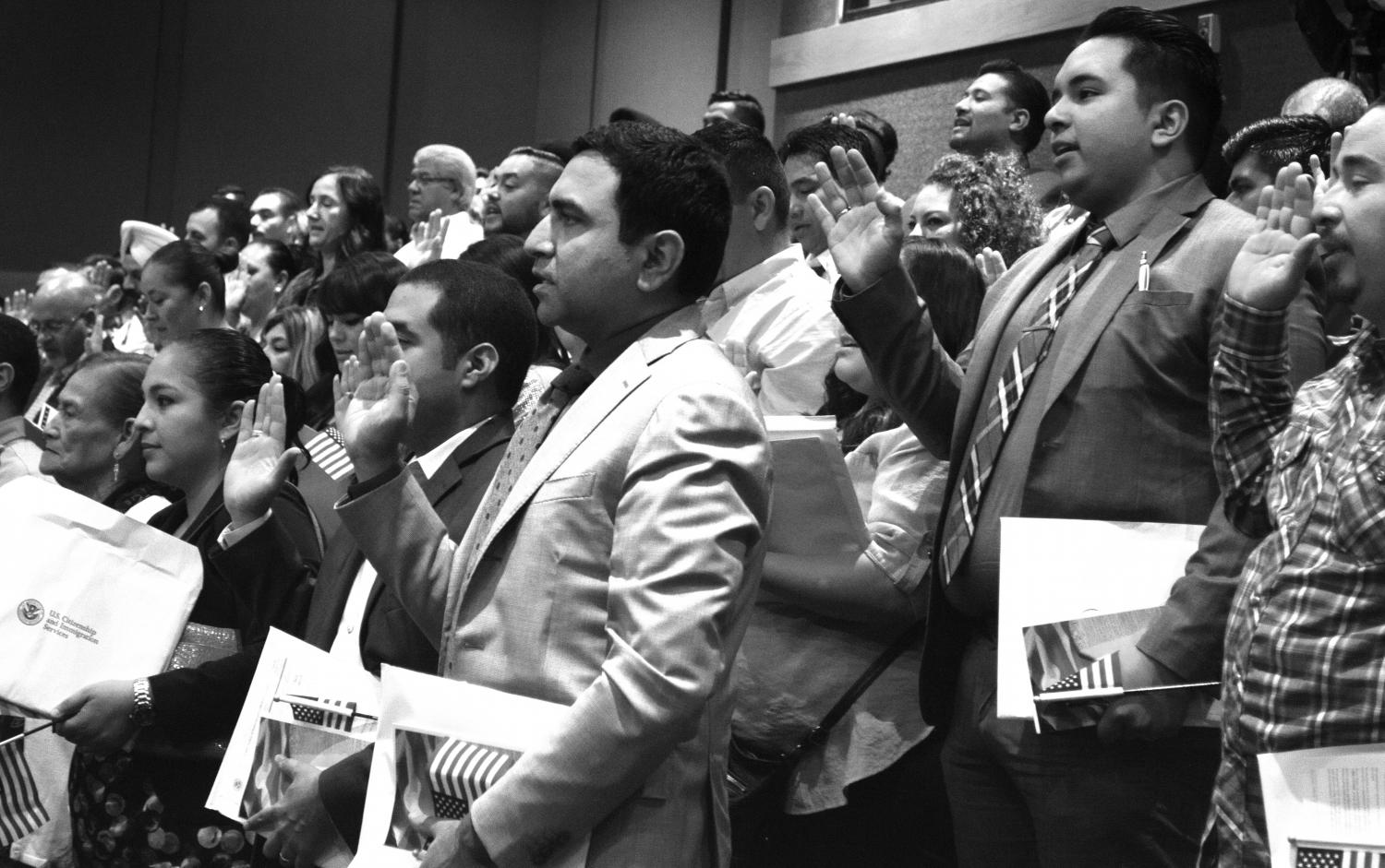 131 people raise their right hands as they swear the Oath of Allegiance and become naturalized citizens at the library.