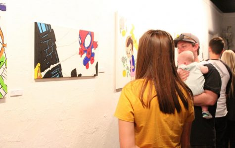 Guests gaze at the artwork of Jason T. Stewart at the Empty Space art exhibit on Sept. 9.