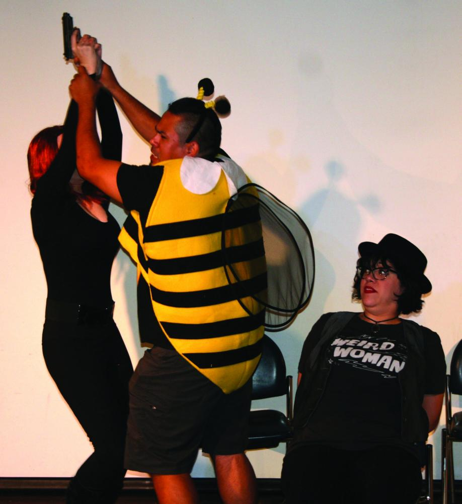 Claire Rock as Black Widow and Jesse Arenas as El Bumblo, struggle for control of the gun, while Alissa Morrow as DJ, looks on in dismay.