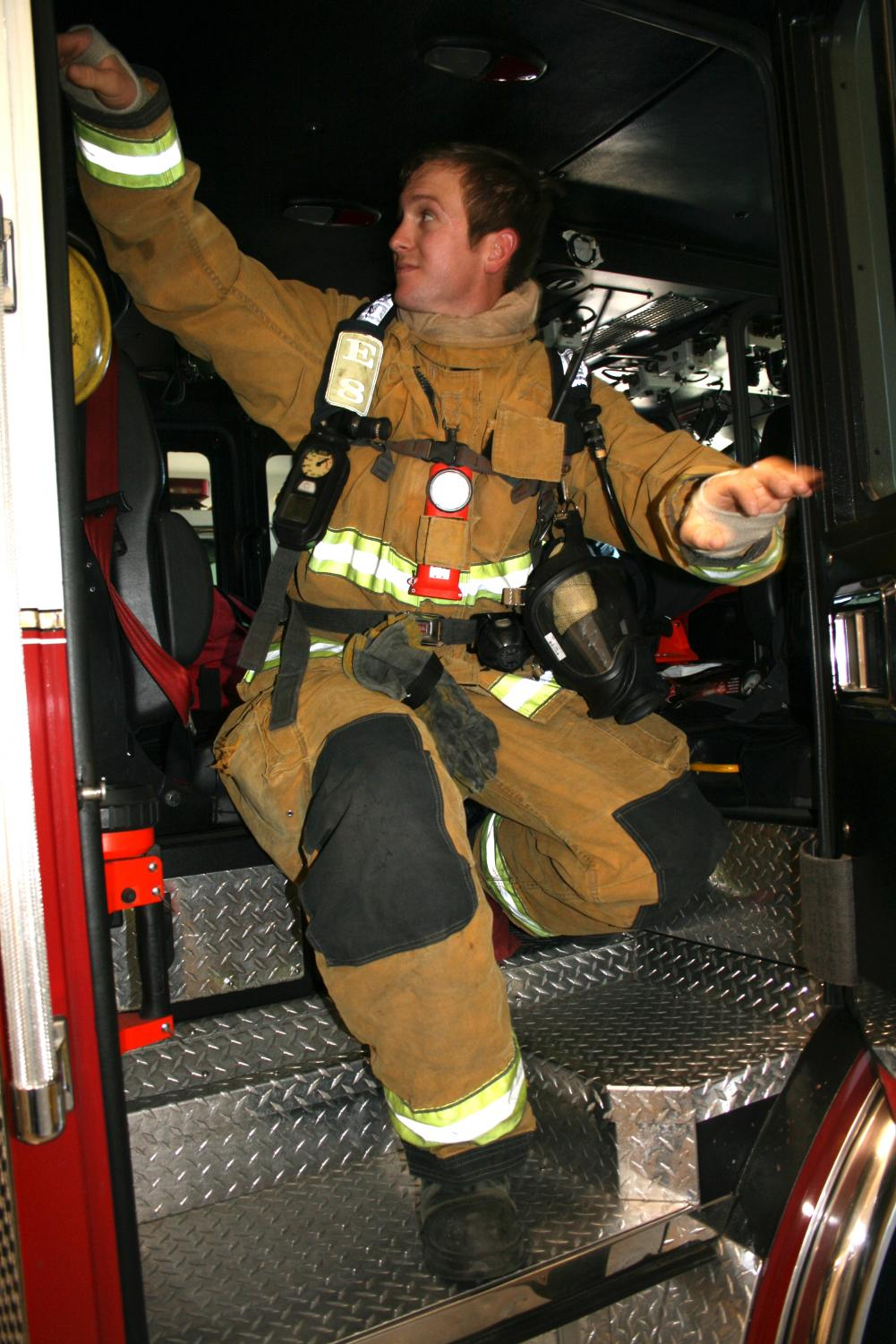 Firefighter Bill Ballard climbs out of a fire engine after demonstrating the routine of responding to a fire call.