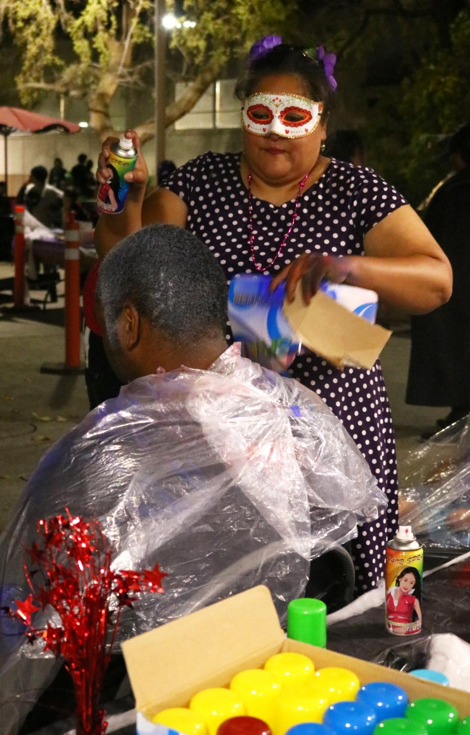 Volunteer Belinda Lopez Rickett at the Masquerade Ball spray paints Jeremey Randall's hair a variety of colors.