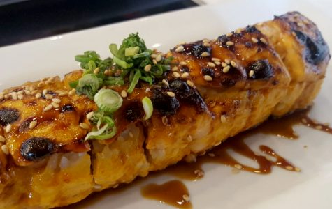 The Baked Salmon Roll dish served at Bocado's Sushi Bar contains salmon, cucumber, crab meat, and cream cheese.
