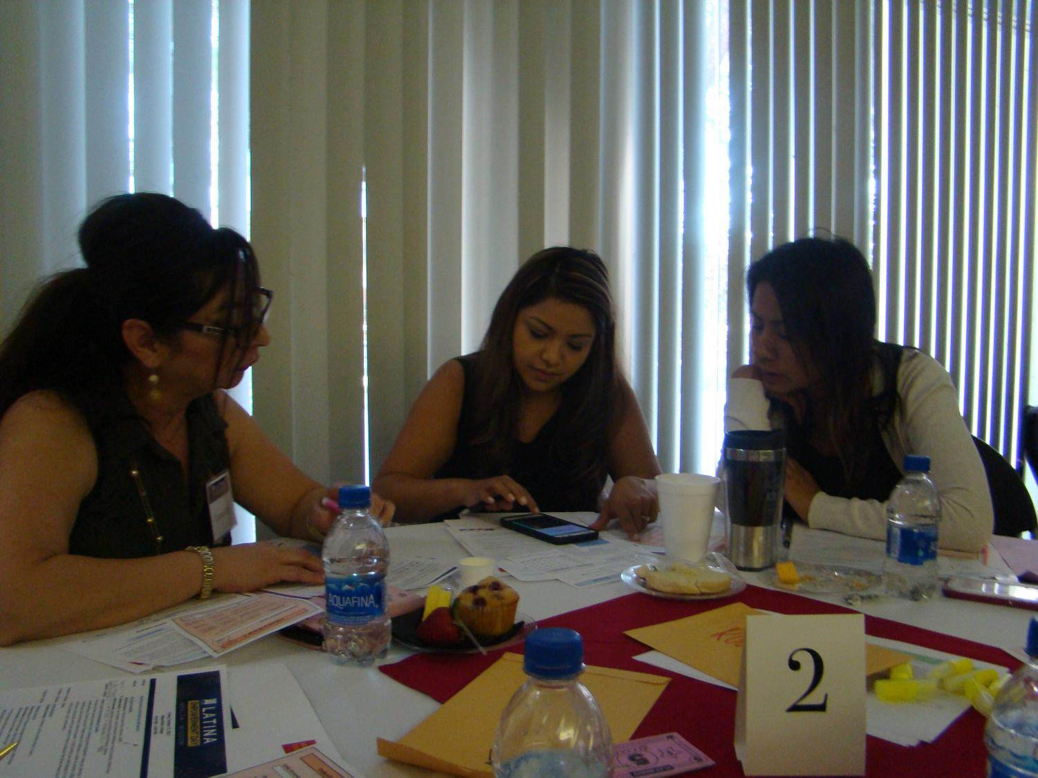 From left to right: Carmen Ruiz, Jhoana Granados, and Briana Rodriguez play a bidding game.