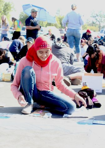 Stockdale High School student Eesha Sohail smiles as she works on her chalk art piece at the local