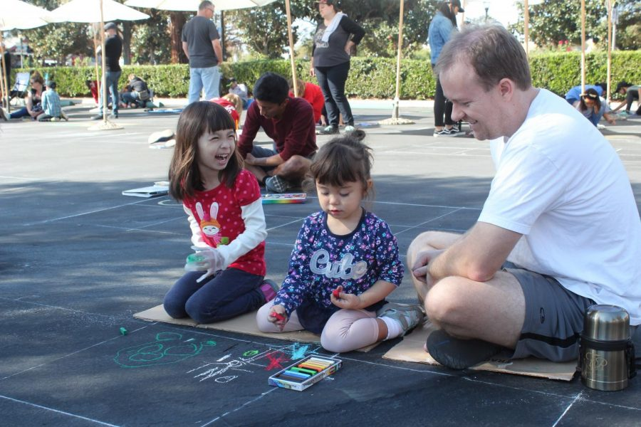 Matt Spencer (far right) looks on as his daughter, Abby spencer (middle), and Sabrina Noakes (far left) try their hand at chalk art at Via Arte.
