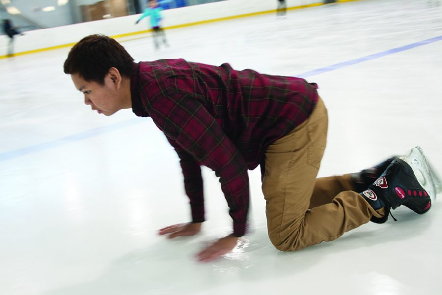 Christopher Cocay steadies himself with his hands as he crawls to the sidelines so he can get back on his feet after a fall resulting in his loose laces made him land painfully on his knees at the ice rink in the Bakersfield Ice Sports Center.