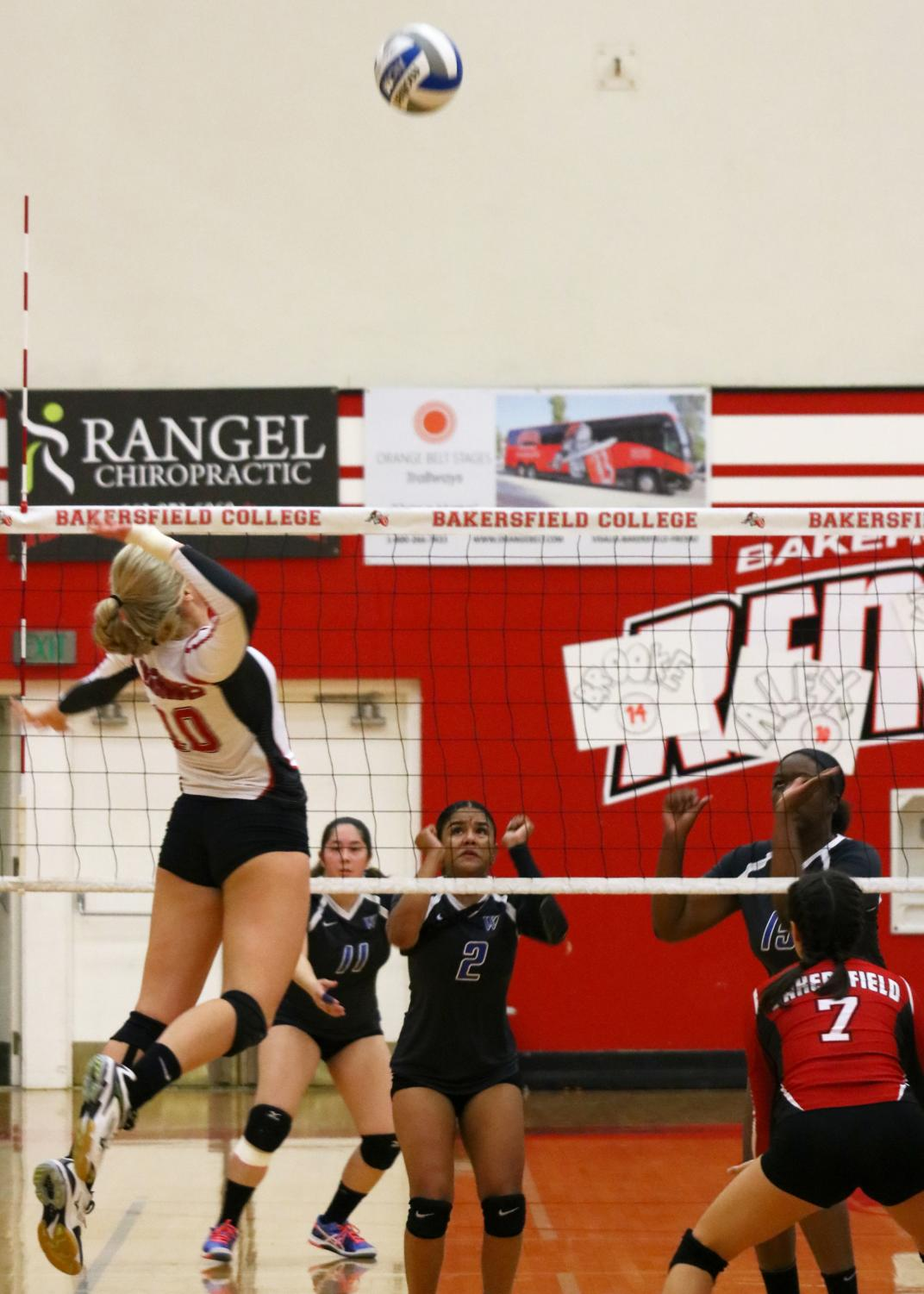 Bakersfield College Volleyball player Alex Paris prepares to spike the volleyball, jumping midair, on West Los Angeles College during a play.