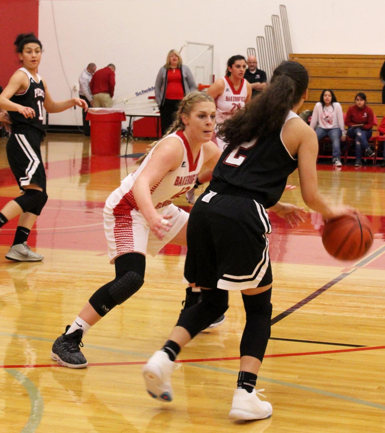 Angie Kroger, BC Renegade player and guard on the basketball team, facing off against a player from Los Angeles Pierce College