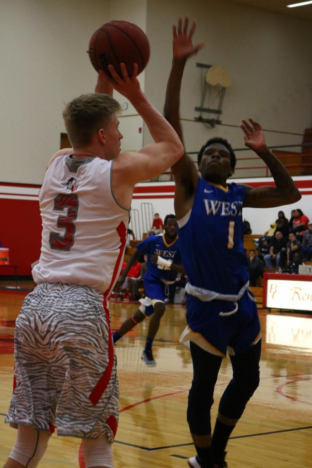 Bakersfield College basketball player Tucker Eenigenburg attempts to shoot and score for the Renegades as an opposing player from West LA tries to block him