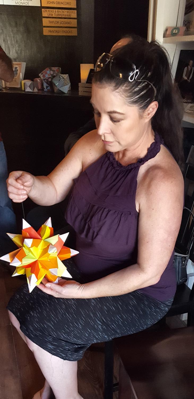 Jennifer Folkert, attendee of the gallery, looks at her geometrix star piece.