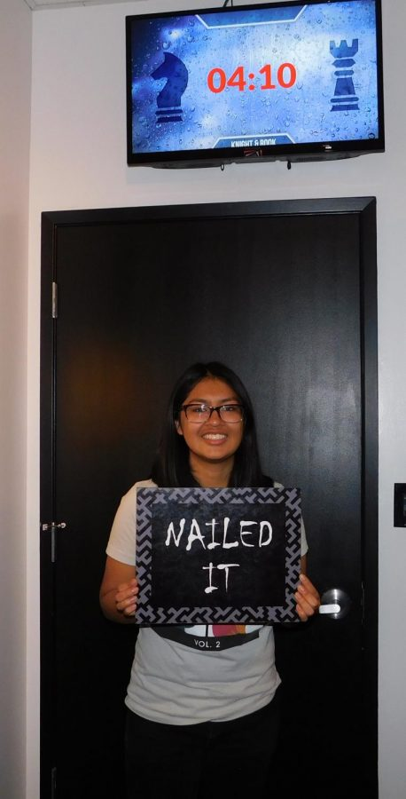 Alexandra Apatiga poses in front of her time and holding a sign saying