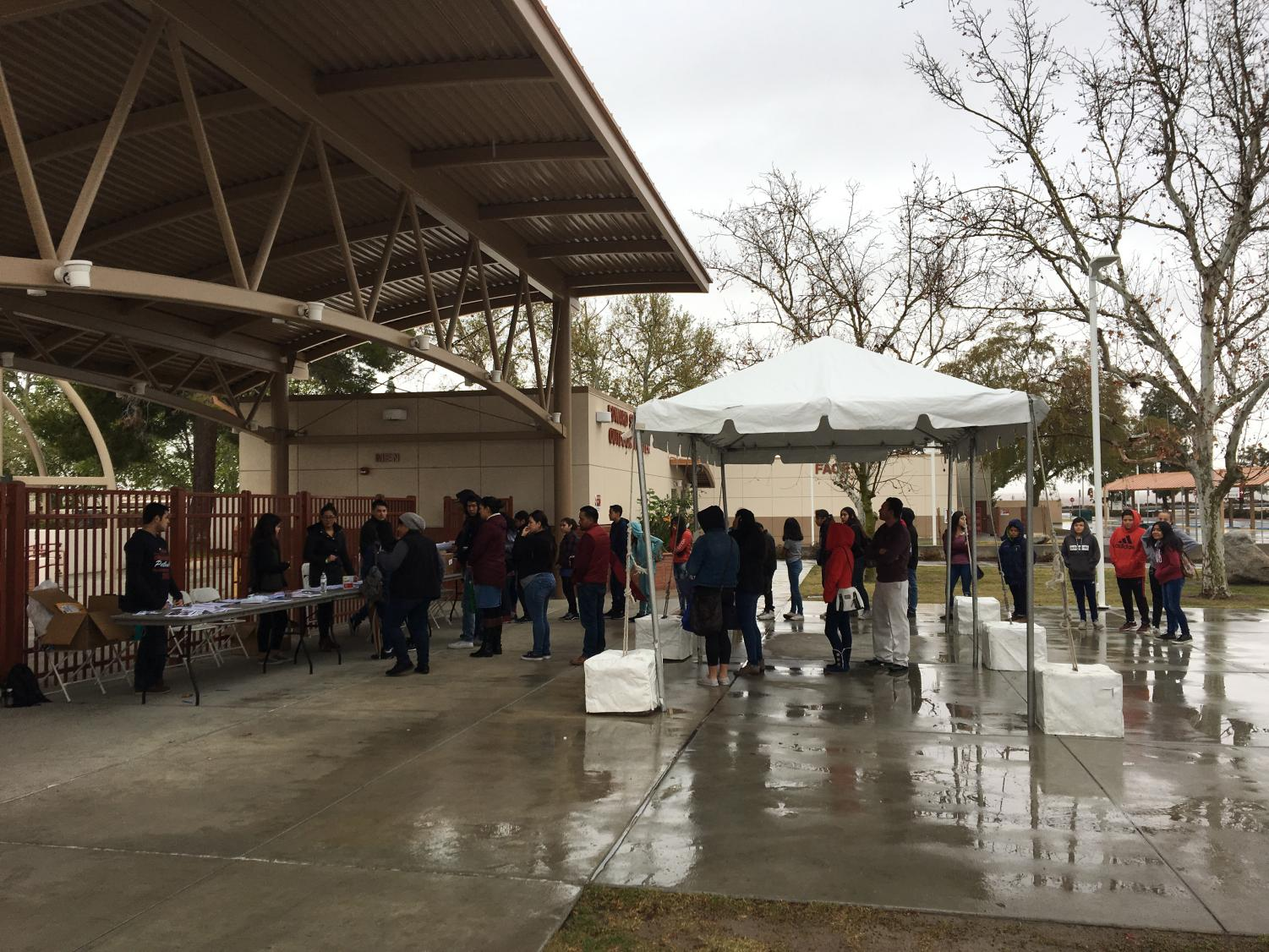 Students and volunteers endure the rain while registering for the second annual STEM and Pre-Health Conference at Bakersfield College.