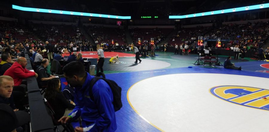 Wrestlers and coaches prepare for their matches before the tournament begins.