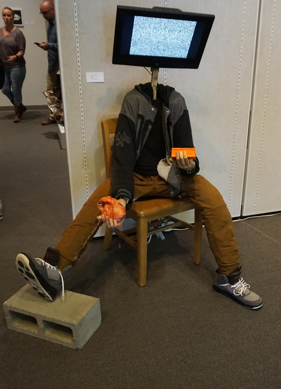 A student summited artwork in the form of a sculpture with a TV for a head.