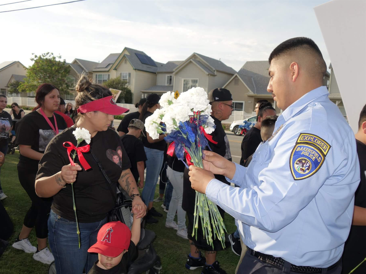 BPD officer gives flowers to marchers