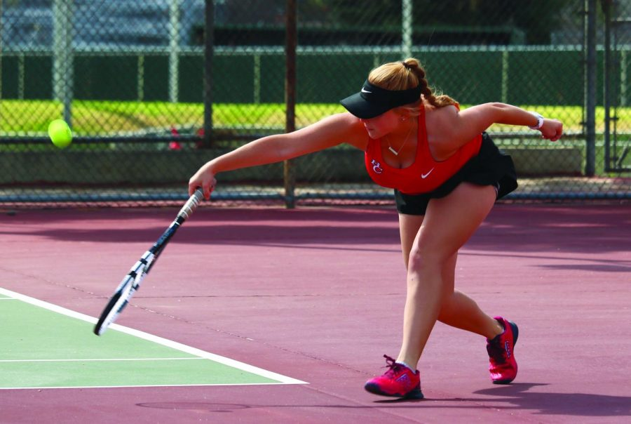 During one of the single matches at the women's BC home tennis game against Santa Monica College, Kenzi Williamson just barely manages to hit the tennis ball across the court to her opponent.