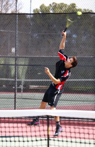 Kaleb Johnson jumping upward in order to reach and return the tennis ball across the court during his singles match against LA Pierce.