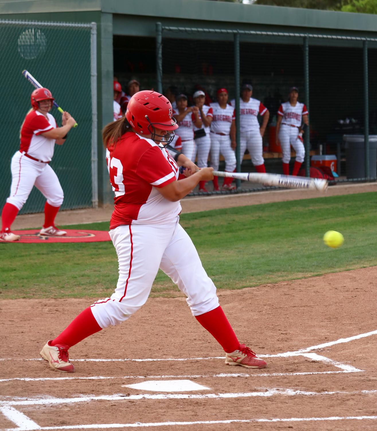 McKenna Valencia of Bakersfield College hitting the softball and running to first base at the home game against Santa Monica College.