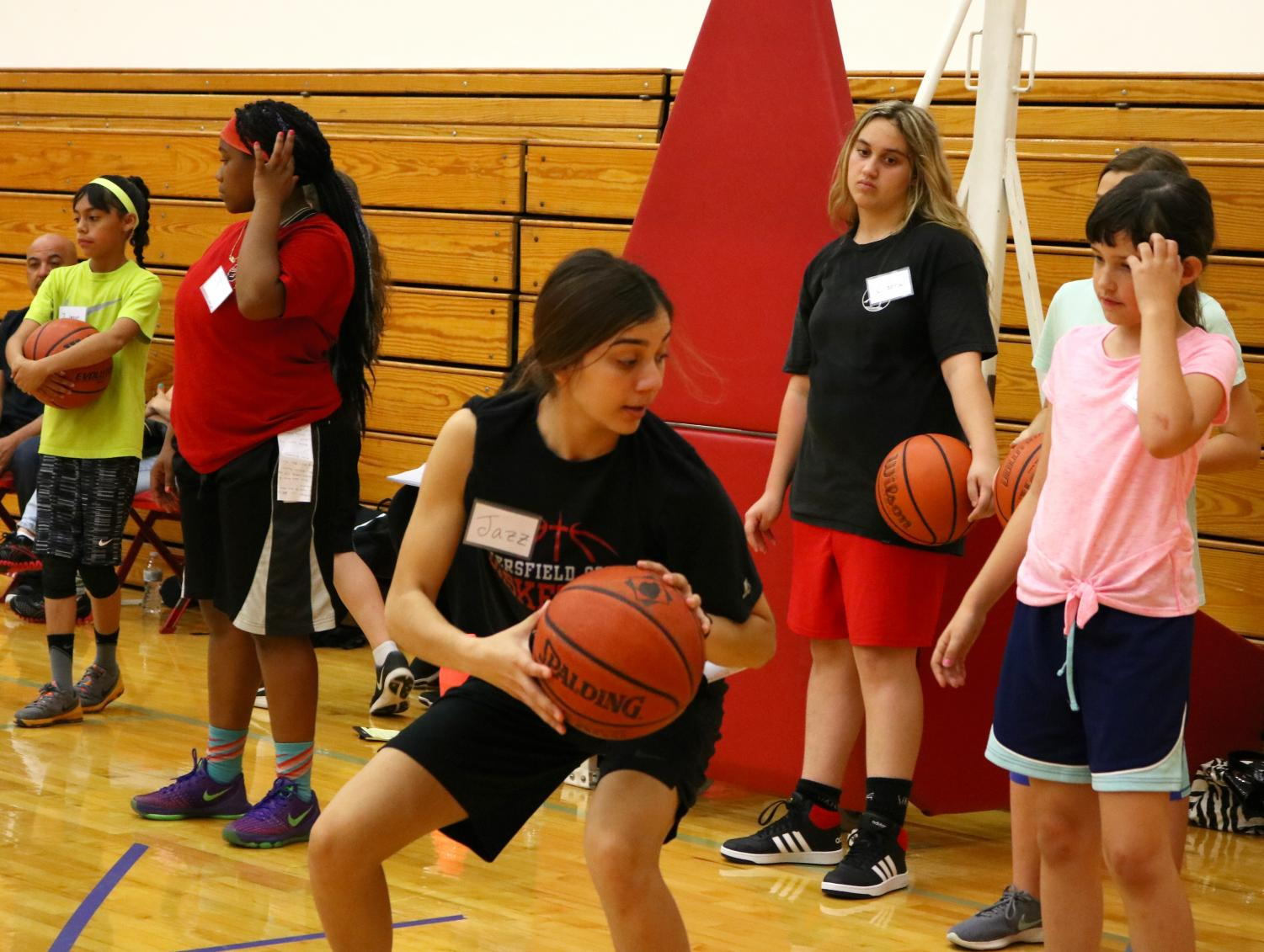 BC student and basketball player Jasmyn Rodriguez showing her group how to crouch and turn without losing balance, as a part of the BC Basketball Academy.