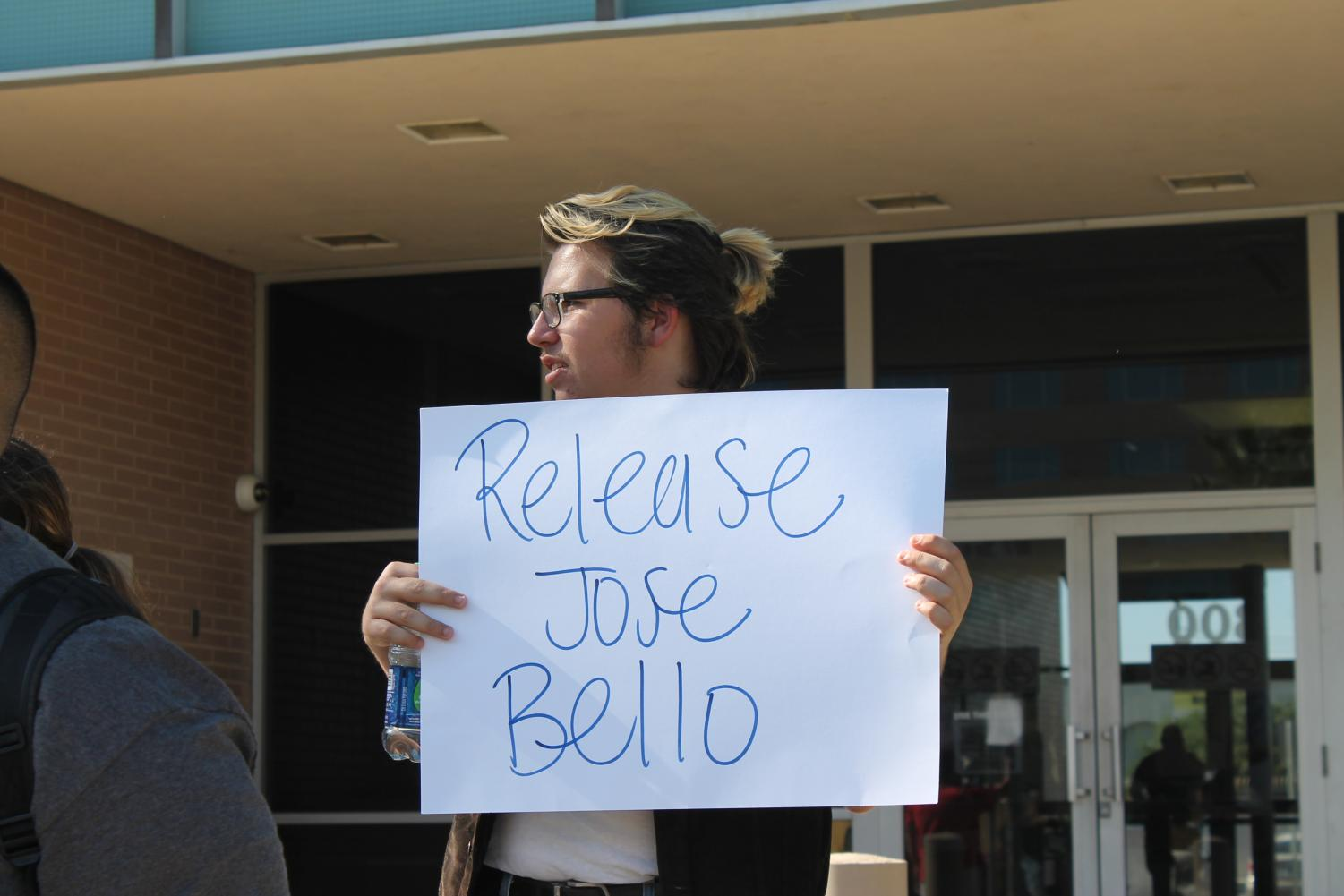 Protester, Chase Wren, holds a sign that says