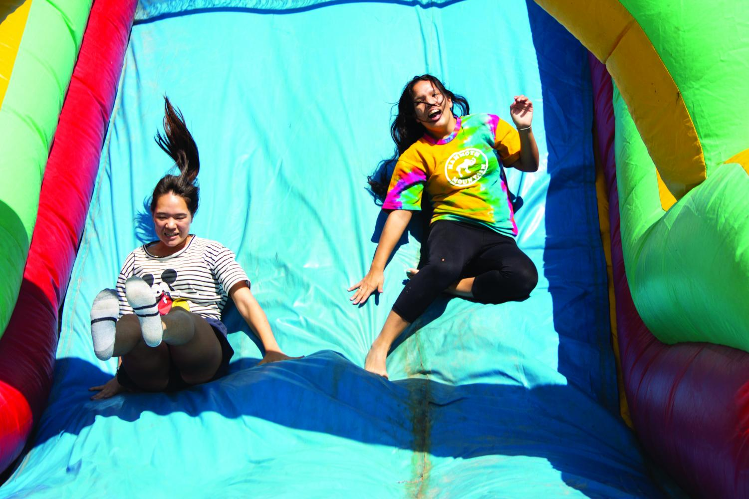 Sheila Kolodji and Dominique Harrison slide down the obstacle course on Aug. 28.
