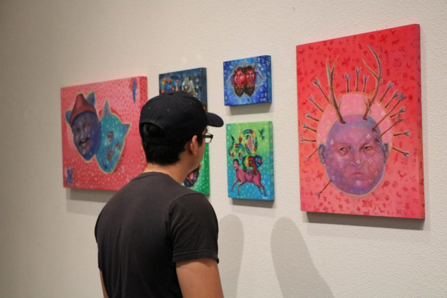 BC student Abel Perez examines Mrbabby's artwork at the May Louise Jones Gallery on Sept. 6.