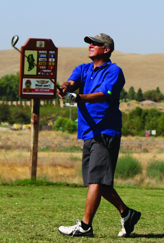 Richard Bumatay watches his golf ball after his swing.