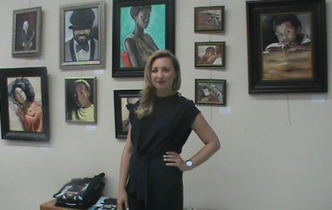 "Artist Victoria Porter poses in front of her ""Black Is Beautiful"" art collection at the Bakersfield Art Association."