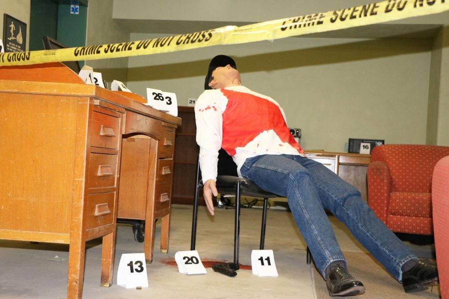 The mannequin behind crime tape at the Crime Scene Lab during CSI week reclines motionless on a chair with a gun on the floor. Numbers are used to label evidence.