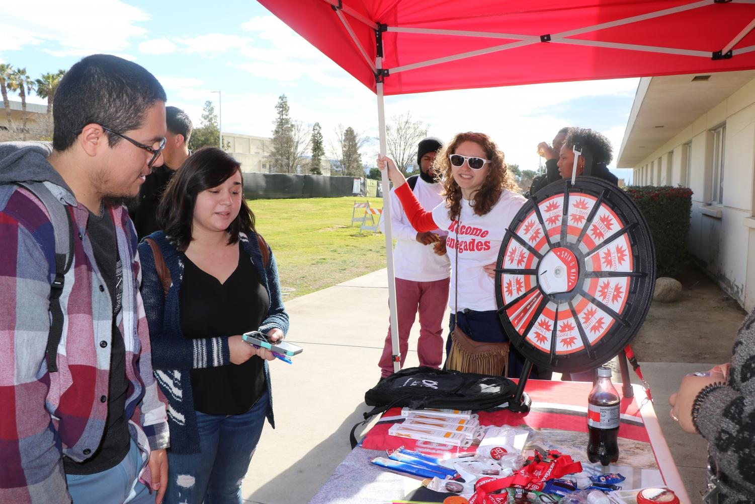 Anthony Acevedo and Naomi Acevedo choose their prizes after spinning the wheel, while ASB member, Elisabeth Sampson (back) looks on.