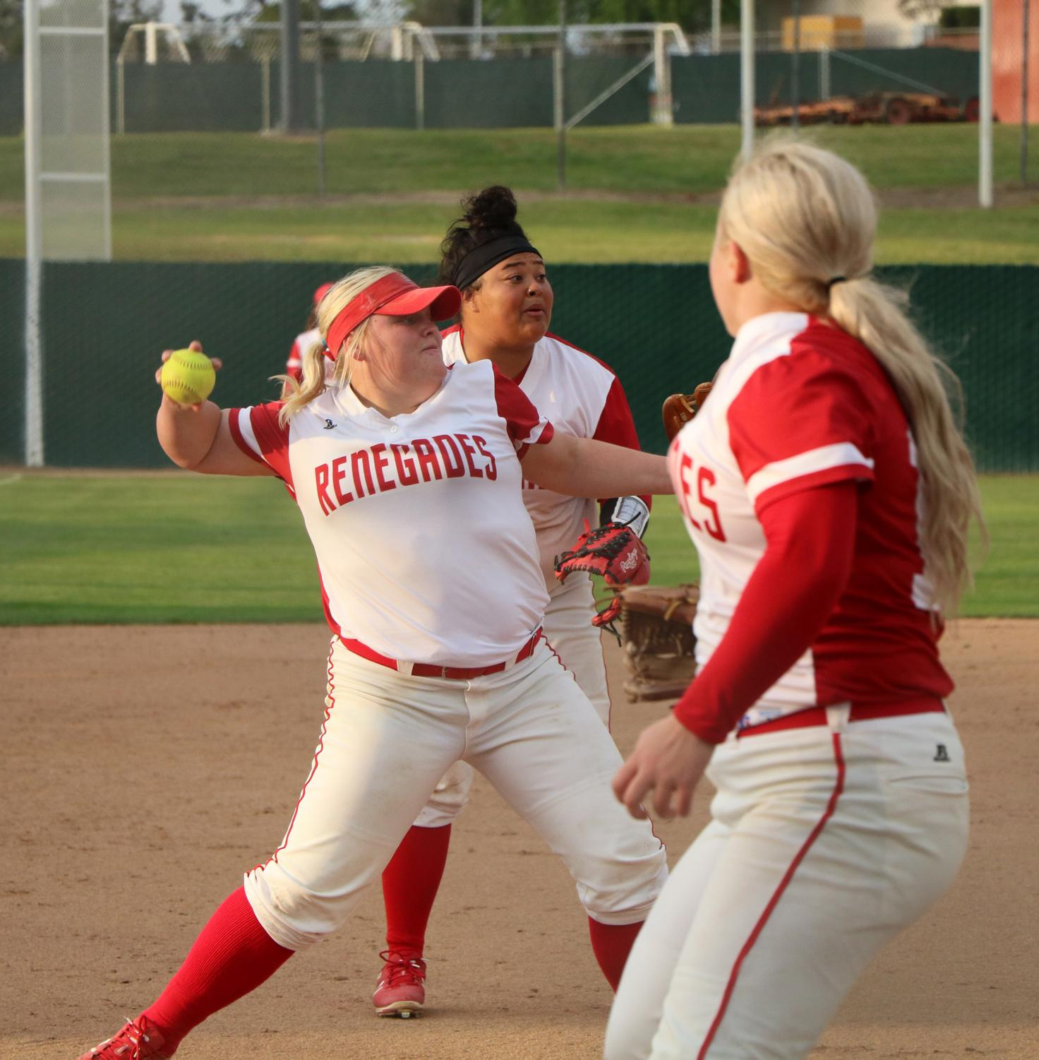 Alantis Rede (furthest back) and Natilee Parrish (close front) watching starter pitcher Kylee Fahy throwing out a bunt ball to first, on March 23.