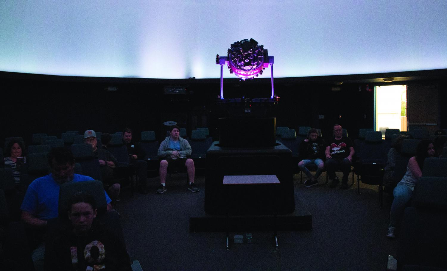 "Viewers gather for the screening of ""Dawn of the Space Age,"" at the William M. Thomas Planetarium on March 28."