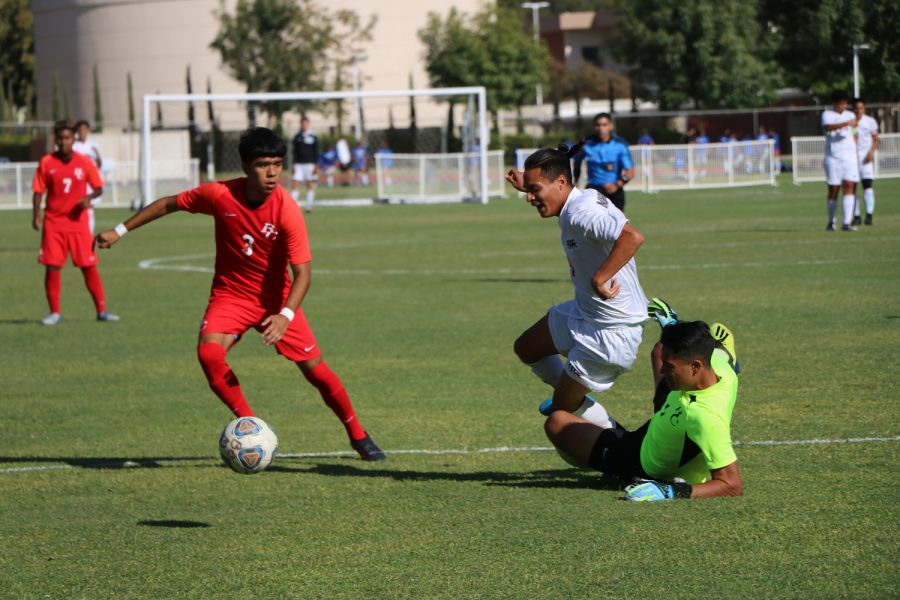 As Armando Alvarez (1) slides to reach the ball, he just misses by an inch running into a player from Antelope Valley, while Edgar Gonzalez rushes to steal the ball before the Antelope Valley player reaches it.